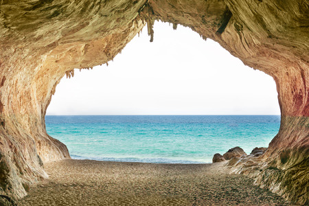 tunnel view: Big empty cave with entrance to blue sea and yellow sandy beach. Europe, Italy, Sardinia