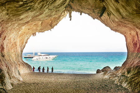 People in the big cave, view from inside to blue sea. Mediterranean coast of Italy, Europe Stock Photo