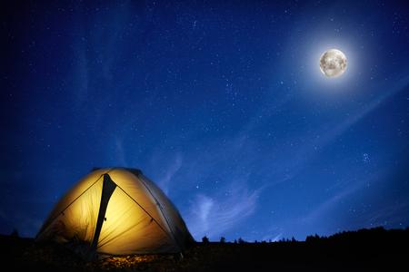 stars night: Illuminated orange camping tent under moon and stars at night Stock Photo