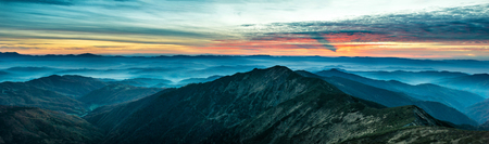 Wide panorama with blue mountains and hills at beautiful sunset