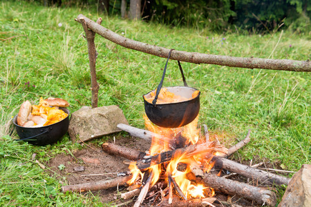 outdoor fireplace: Cauldron with cooking boiling edible mushrooms on the fire. Outdoor fireplace in a camp