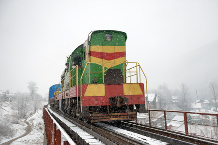 heavy snow: Locomotive of cargo on the bridge near winter forest with trees in snow Stock Photo