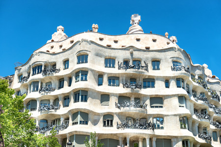 BARCELONA, SPAIN - May 21, 2016: Facade of Casa Mila with green trees on the street of Barcelona, Spain. Famous building designed by Antoni Gaudi Editorial