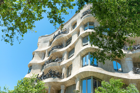 BARCELONA, SPAIN - May 21, 2016: Facade of Casa Mila with green trees on the street of Barcelona, Spain. Famous building designed by Antoni Gaudi, included in the UNESCO list