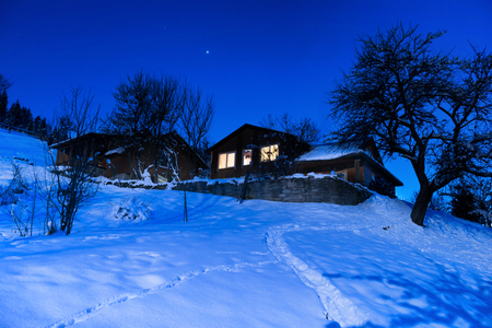 yule log: Wooden country house in snow at winter night under blue dark sky with stars
