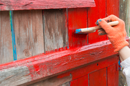 A painter hand painting wooden fence with red color