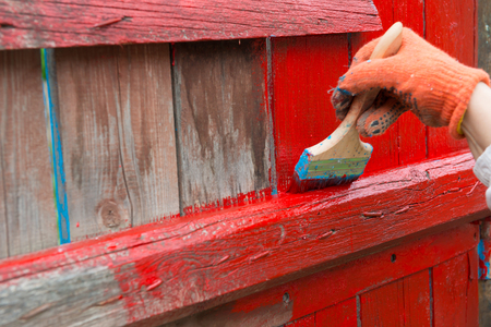 wooden color: A painter hand painting wooden fence with red color