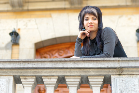 mujer bonita: Pretty young woman in black dress on the balcony of luxury castle