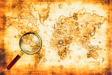 Old map with an magnifying glass explored it. Vintage travel background Stock Photo
