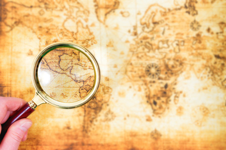 Old map and magnifying glass in a hand explored it. Vintage travel background