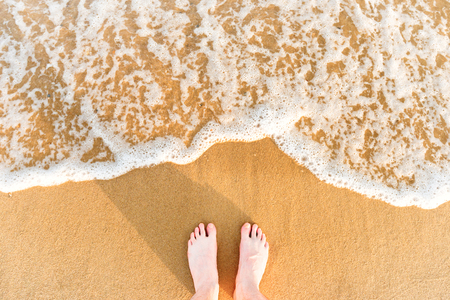 sun down: Womans feet on yellow beach sand with sea wave and white foam