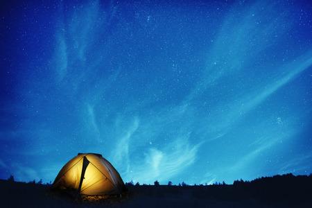 Illuminated yellow camping tent under many stars and at night