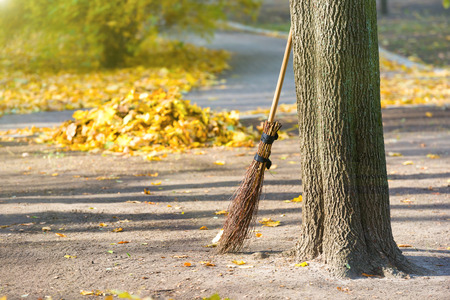 Cleaning in the autumn park - broom with pile of yellow fallen leaves