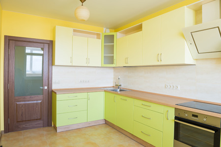 stainless: Kitchen interior in modern apartment. Light yellow empty sunny room