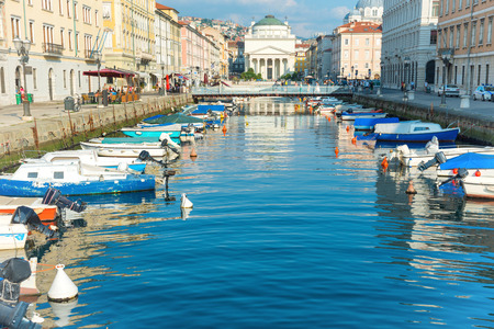 Cityscape and canal with boats in city of Trieste, Italy