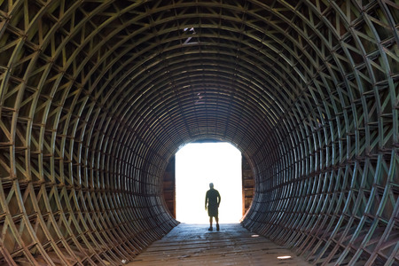Silhouette of a man and light in the end of dark tunnel