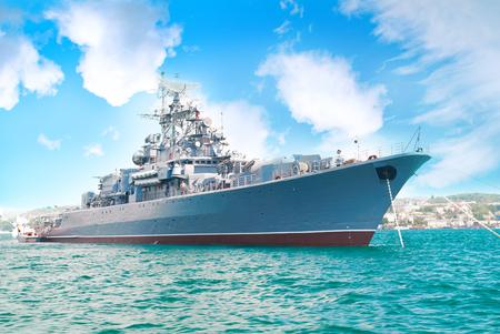 Navire militaire dans la baie avec ciel bleu et nuages