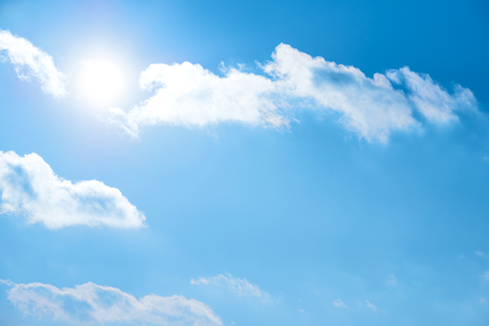 Sun on the blue sky with clouds