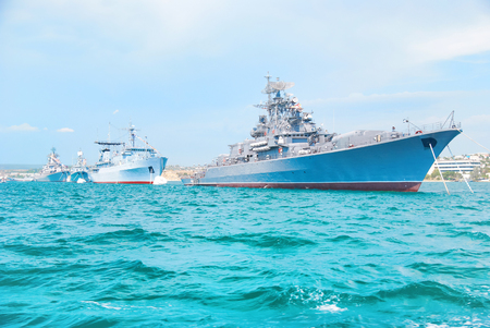 Military navy ships in order on blue sea