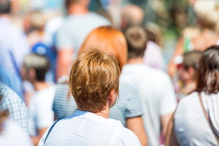 Woman in crowd of people on city street Banco de Imagens
