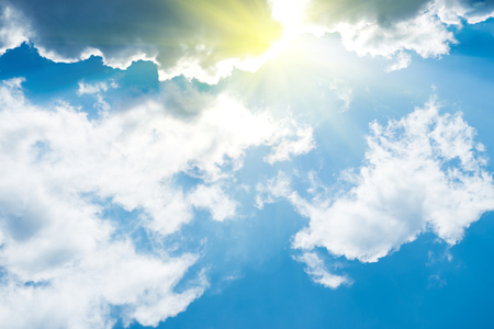 White fluffy clouds on the blue sky with sun rays. Nature background