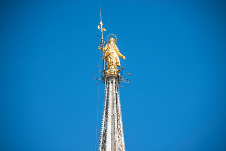 Golden Virgin Mary statue on top roof of Duomo cathedral in Milan, Italy Banco de Imagens