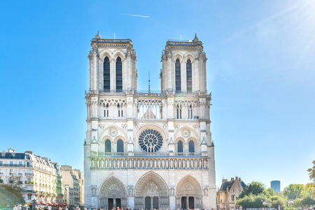 Notre Dame de Paris - people at famous cathedral with sun and blue sky