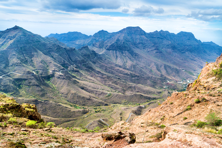 Nature landscape of Canary Island with mountain range, green hills and curvy road Archivio Fotografico