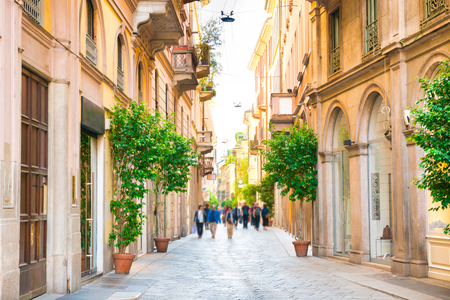 Narrow street with walking people and trees in ceramic pots in Milan, Italy Standard-Bild