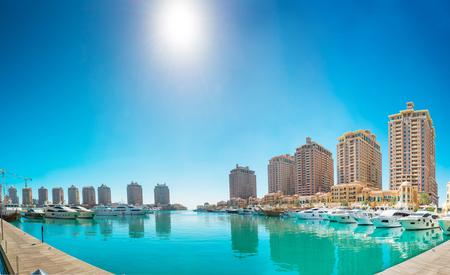Panorama of luxury residential buildings of Pearl Qatar and white yachts at Porto Arabia marina. Doha, Qatar