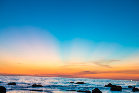 Beautiful colorful sunset landscape with sand beach, golden sun and stones at sea shore