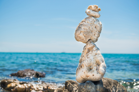 Zen stones balance at stony beach and sea background