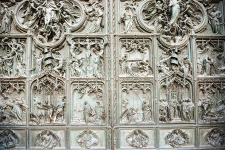 Forged doors with bronze bas reliefs at facade of cathedral Duomo di Milano. Italy Archivio Fotografico