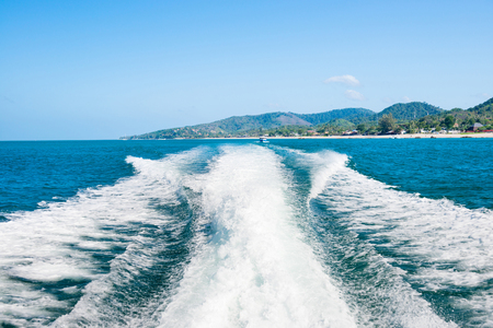 Wake of cruise boat on water surface and horizon with blue sea and island coast at background