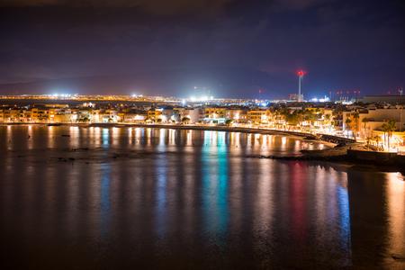 Vista nocturna de la ciudad costera iluminada de Arinago. Gran Canaria, España