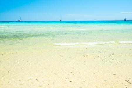 Spiaggia di sabbia bianca e acqua di mare limpida sotto il cielo blu. Può essere usato come sfondo per le vacanze estive Archivio Fotografico