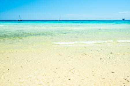 Wit zandstrand en helder zeewater onder de blauwe hemel. Kan worden gebruikt als achtergrond voor de zomervakantie Stockfoto