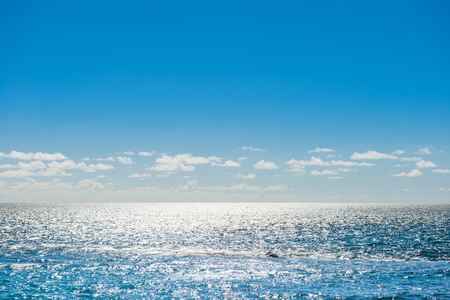 Paisaje marino con reflejo plateado de la luz del sol, olas tranquilas, cielo brillante y nubes blancas