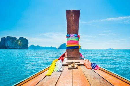 Vista dalla testa della barca di legno tradizionale al mare blu e alle isole tropicali Archivio Fotografico