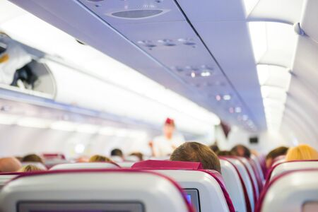 Interior del avión con pasajeros en asientos esperando para despegar y azafata en uniforme caminando por el pasillo