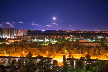 Night city panorama with urban landscape and illuminated buildings under moon and night sky. Kiev Zdjęcie Seryjne