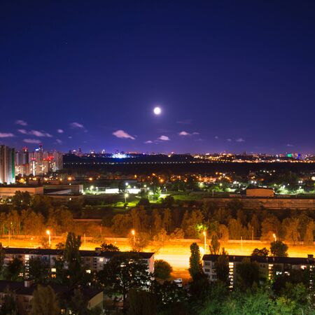 Night city panorama with urban landscape and illuminated buildings under moon and night sky. Kiev 写真素材