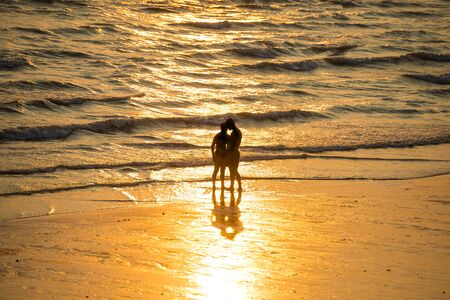 Silhouettes of people walking on beach and taking photo at beautiful sunset