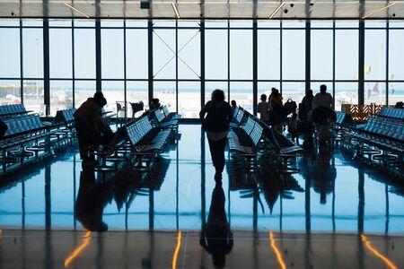 공항에서 실루엣 사람들의 그룹은 수하물로 등록하러 간다 스톡 콘텐츠