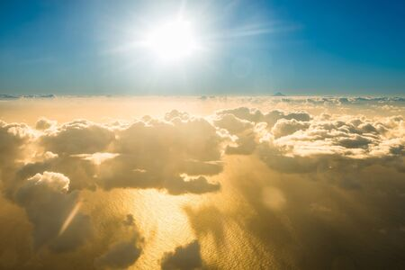 Airplane view of beautiful landscape with gold colored clouds, ocean with mountain peak and bright shining sun