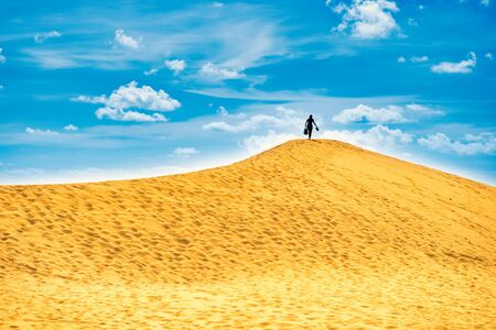 Sandy landscape with silhouette woman on top of dune. Natural reserve Maspalomas Dunes, Gran Canaria, Spain