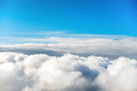 Cloudscape with clear blue sky and fluffy clouds, view from above