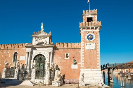 Facade of Venetian Arsenal with tower, gate and statues. Venice, Italy