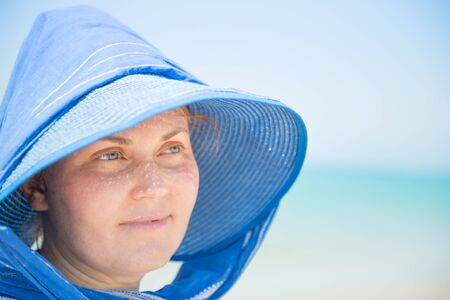 Woman in blue hat on blue sky and water background. Vacation concept