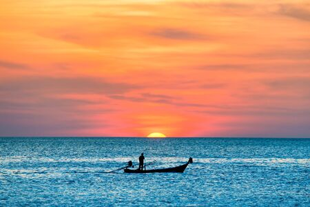 View of traditional fishing boat in blue sea during beautiful orange sunset Stockfoto